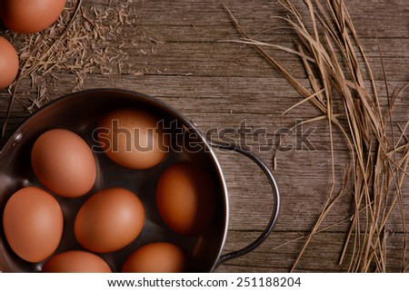 chicken eggs in pan on rustic wooden background with straw - stock photo