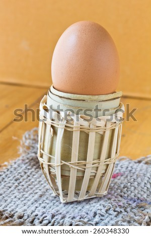 Chicken eggs in the bamboo basket over sack - stock photo