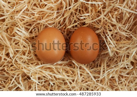 Chicken eggs in the nest of straw.