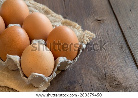 Chicken eggs in the package on the old wooden table - stock photo
