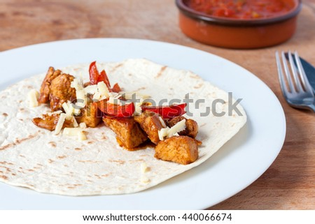 Chicken fajita mix topped with grated cheese laying on an open flour tortilla - stock photo