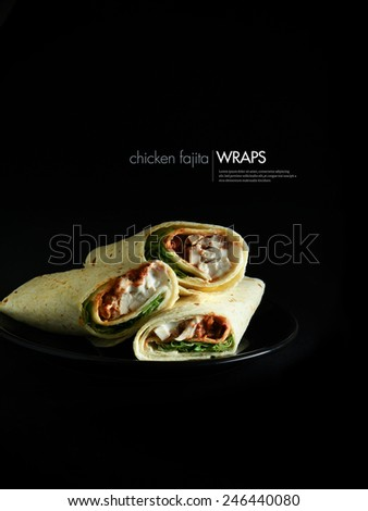 Chicken Fajita wraps isolated against a black background. Copy space.  - stock photo