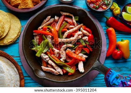 chicken fajitas in a pan with sauces chili and sides Mexican food - stock photo