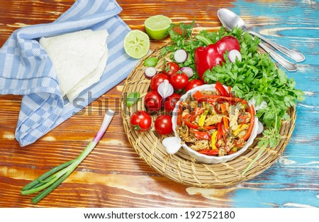 Chicken Fajitas. Strips of grilled chicken breast with sauteed peppers and onions, served with flour tortillas and salsa - stock photo