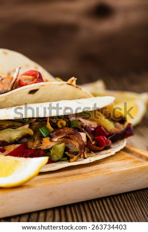 Chicken fajitas with grilled onions and bell peppers and serve with flour tortillas on rural wooden board