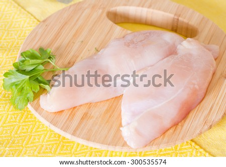 Chicken fillet and parsley leaves on a cutting board