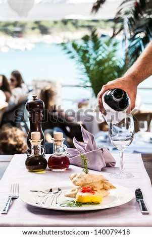 chicken fillet and potato fritter gourmet dish with a crisp glass of wine being poured by the waiter - stock photo