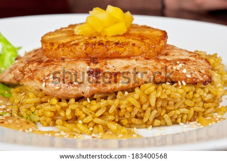 chicken fillet baked with pineapple, with rice and salad - stock photo