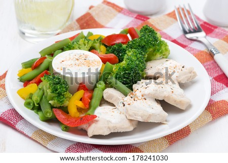 chicken fillet, steamed vegetables and yoghurt sauce on a plate, close-up