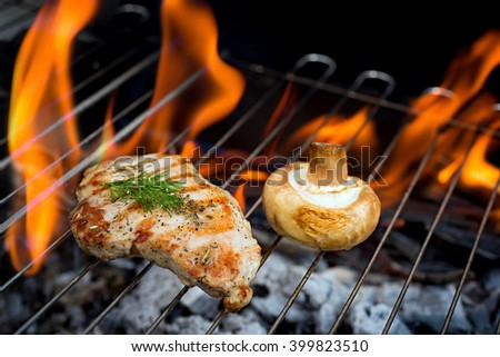 chicken fillets on the barbecue with flame on background