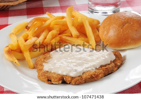 Chicken fried steak with country gravy and french fries - stock photo