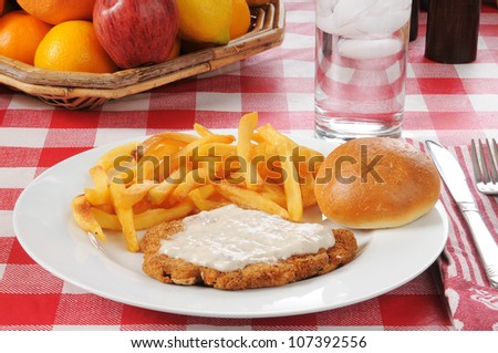 Chicken fried steak with fries and a basket of fruit