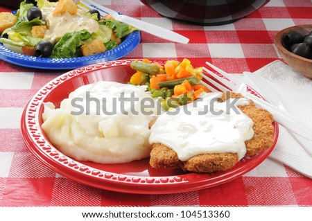 Chicken fried steak with mashed potatoes and country gravy on a picnic table - stock photo