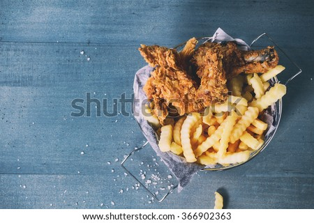 Chicken fries strips and legs with French fries in metal basket over blue wooden table with sea salt. Top view. With retro filter effect