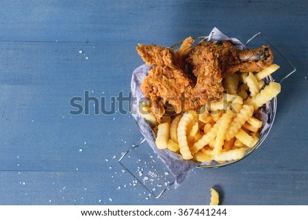 Chicken fries strips and legs with French fries in metal basket over blue wooden table with sea salt. Top view - stock photo