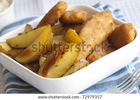 Chicken goujons with roast potato wedges in a bowl