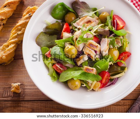 Chicken healthy salad on a rustic wooden table. Top view