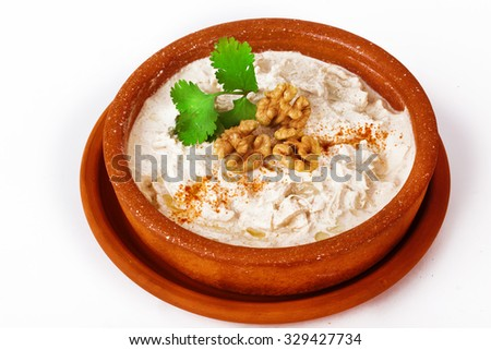 chicken in a creamy sauce with parsley and walnuts in a pot on a white background for the menu - stock photo
