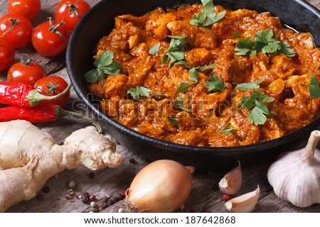 Chicken in curry sauce in a pan with the ingredients on the old desk  - stock photo
