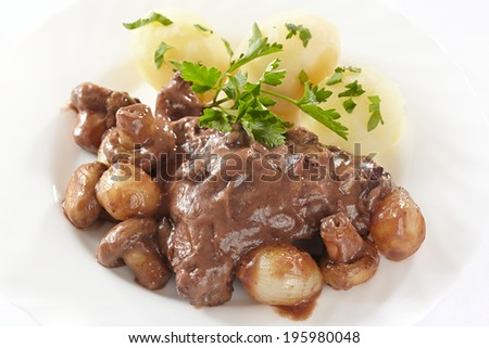 Chicken in red wine with onions, mushrooms and bacon - stock photo