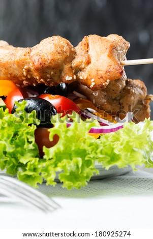 Chicken kebab over salad - stock photo