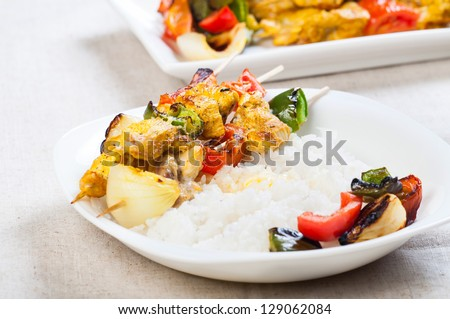 chicken kebab plated with buttered rice and vegetables on a side - stock photo