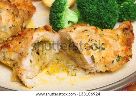 Chicken kiev dinner with broccoli and roast potatoes - stock photo