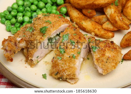 Chicken Kiev served with potato wedges and peas. - stock photo