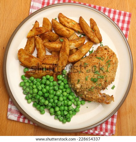 Chicken Kiev served with potato wedges and peas.