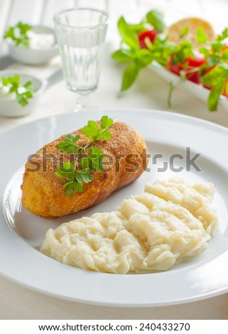 chicken Kiev with mashed potatoes.�  Chop chicken fillet stuffed with juicy butter, cheese and greens on a white plate - stock photo
