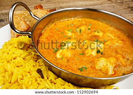 Chicken Korma a popular sweet indian curry dish of coconut and cream sauce served in a dish on a plate with pilaf rice and samosas - stock photo