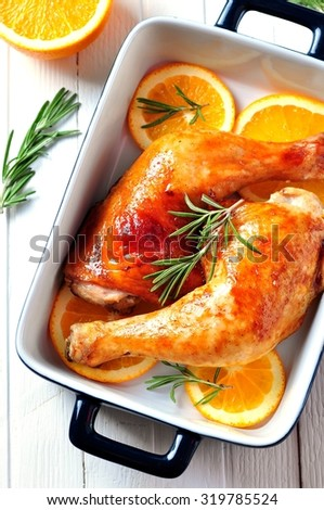chicken leg roasted with olive oil, balsamic vinegar and soy sauce with orange slices, rosemary, pepper and sea salt - stock photo