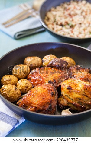 chicken leg with potato on pan and served with rice