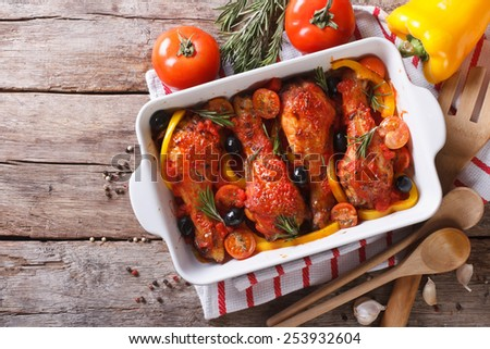 Chicken legs baked in tomato sauce with vegetables. horizontal view from above  - stock photo