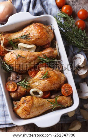 chicken legs in a baking dish and ingredients close-up on the table. vertical top view  - stock photo
