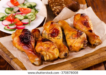Chicken legs on a wooden board with fresh vegetable salad - stock photo