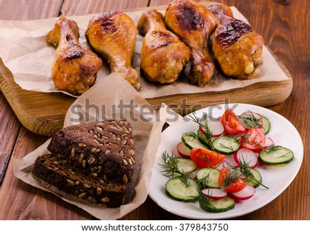 Chicken legs on a wooden board with fresh vegetable salad