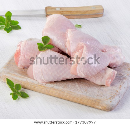 chicken legs on a wooden platter. selective focus