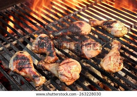 Chicken Legs On The Hot Barbecue Grill. Flame Of Fire On The Background. - stock photo