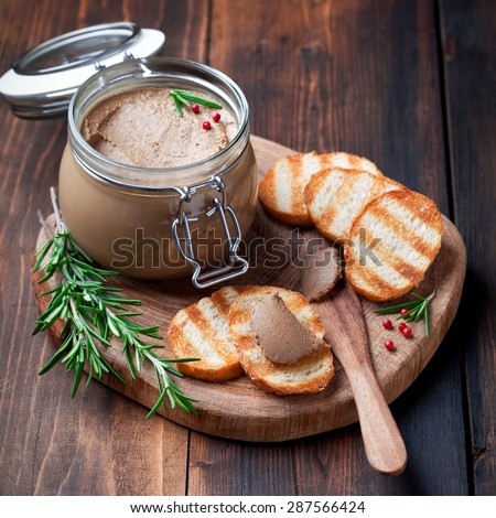 Chicken liver pate in jar and on bread, selective focus - stock photo