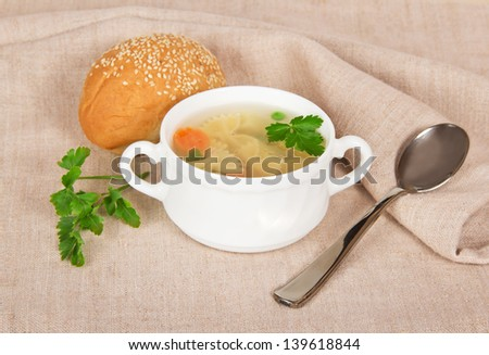 Chicken macaroni soup, bread and spoon on a sacking - stock photo