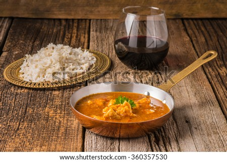Chicken Madras served with a glass of red wine. - stock photo