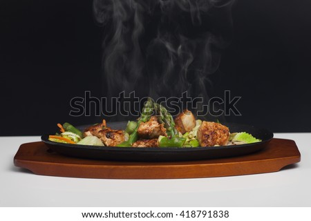 chicken meat with asparagus in a sizzler