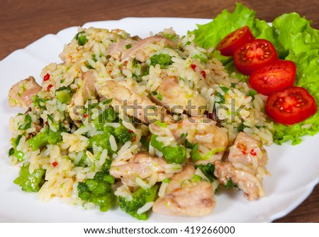 chicken meat with rice and broccoli in a plate on wooden table - stock photo
