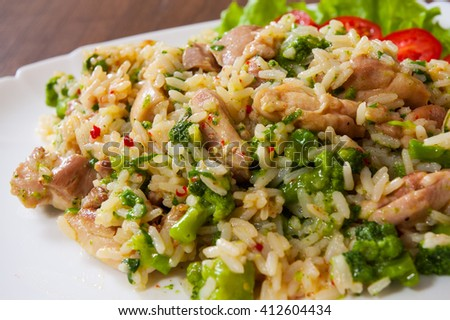 chicken meat with rice and vegetables in a plate on wooden table - stock photo