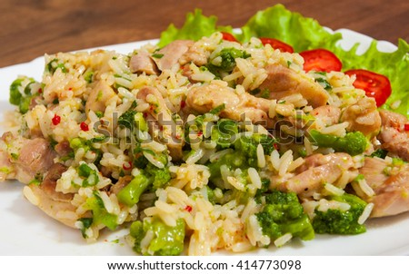 chicken meat with rice and vegetables in a plate on wooden table