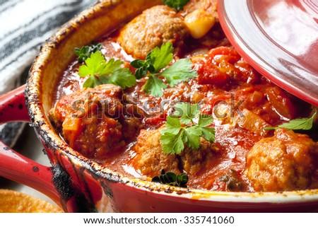 Chicken meatballs in tomato sauce, cooking in red casserole dish. - stock photo