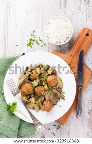 Chicken meatballs with oyster mushrooms, zucchini and rice on white plate and wooden cutting board.  Healthy food concept.  Top view. - stock photo