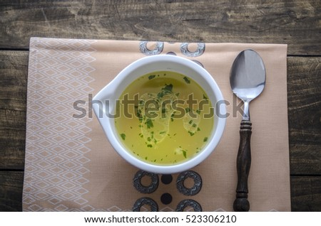 chicken noodle soup on wooden table, from above