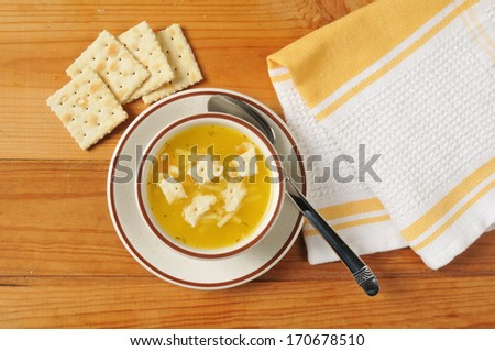 Chicken noodle soup with saltine crackers shot from above - stock photo
